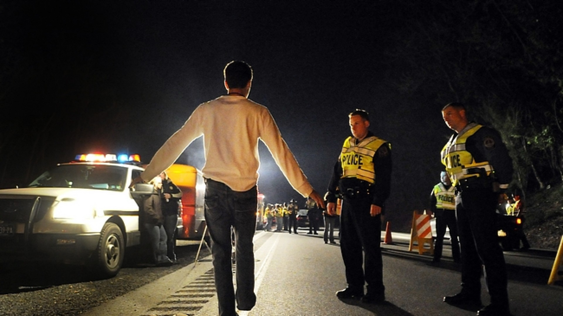West Manchester Township Police Officer Adam Bruckhart, left, and York Area Regional Police Officer Mike Georgiou observe a driver suspected of being under the influence of alcohol as he performs a field sobriety test at a DUI checkpoint on the business loop of Interstate 83 Friday, April 23, 2010. The driver was later arrested on suspicion of DUI. DAILY RECORD/SUNDAY NEWS - KATE PENN